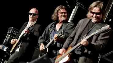 Her ses Johnny Madsen omringet af to dygtige musikere, men vidste du at Johnny selv sagtens kunne være den bedste guitarist af de tre?