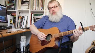 Snapshot af guitarunderviser Fridrikur Ellefsen der viser hvordan man spiller en fingerstyle udgave af Pianomand